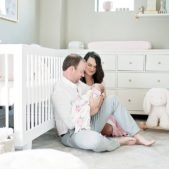 dad and mom hold newborn baby girl in nursery
