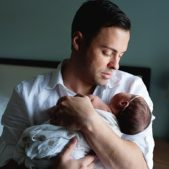 a dad holds his newborn daughter close to his chest
