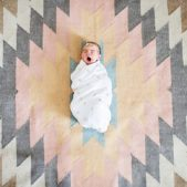 newborn baby girl yawns big while swaddled and laying on a rug