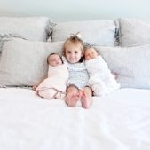 a big sister holds her twin sisters during their newborn session