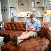 a new dad sits on a chesterfield sofa holding his newborn son
