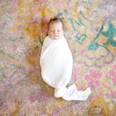 Baby lays swaddled on a brightly colored rug